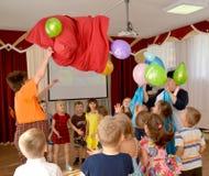 Kaliningrad, Rússia O animador no terno do ` s de Carlson derrama para fora balões de um saco Um feriado no jardim de infância fotografia de stock royalty free