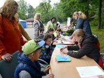 Kaliningrad, Rússia O professor mostra ao dobramento das crianças do origâmi Classe do mestre do ` s das crianças no ar livre Foto de Stock Royalty Free