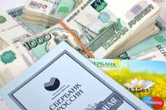 Kaliningrad, Rússia Os blocos de notas de mil-rublo, economias registram e cartão plástico de Sberbank de Rússia Imagens de Stock Royalty Free