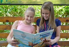 Kaliningrad, Rosja Dwa dziewczyny dziewczyny z uśmiechem rozważają książkę na ławce Rosyjski tekst - Gulliver ` s Podróżuje Zdjęcie Stock
