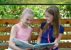 Kaliningrad, Rosja Dwa rozochoconej dziewczyny czytają książkę na ławce Rosyjski tekst - Gulliver ` s Podróżuje Obraz Royalty Free