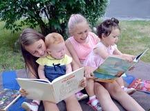 Kaliningrad, Rosja Dzieci różny wiek z entuzjazmem rozważają książki, siedzi na trawie w ogródzie zdjęcia royalty free