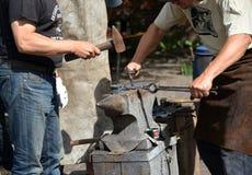 Kaliningrad, Rússia Dois smiths forjam um metal Imagem de Stock Royalty Free