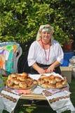 KALININGRAD, RUSLAND - AUGUSTUS 15, 2014: De vrolijke vrouw in een nationaal kostuum verkoopt broodjes bij markt van nationale cr Royalty-vrije Stock Afbeeldingen
