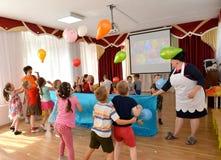 Kaliningrad, Rusland De kinderen werpen ballons tijdens de vakantie in kleuterschool Stock Fotografie