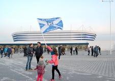 Kaliningrad, Rusland De meisjesgolven een vlag van ffootballclub Baltika tegen de achtergrond van Baltisch Arenastadion royalty-vrije stock fotografie