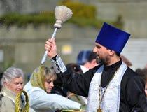 Kaliningrad, Rusland De orthodoxe priester zegent gelovigen met de hulp aspergillum Pasen-traditie Stock Afbeelding