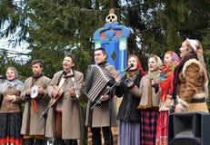 Kaliningrad, Rusland De uitvoerders van folkloreensemble spreken in het park bij de viering van Maslenitsa royalty-vrije stock foto