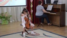 Kaliningrad, Rusland Het meisje speelt een violoncel Ochtendprestaties in kleuterschool stock footage