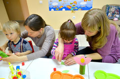 Kaliningrad, Rusland Kinderen en moedersstok samen toepassingen in studio van creatieve ontwikkeling Royalty-vrije Stock Afbeeldingen