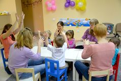 KALININGRAD, RUSSIA. Small children play with parents, sitting at a table. Studio of creative development royalty free stock image