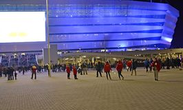 KALININGRAD, RUSSIA. The audience and volunteers about the shining Baltic Arena stadium late evening Royalty Free Stock Images