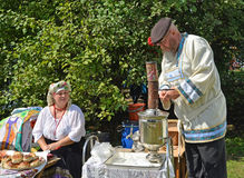 KALININGRAD, RUSSIA - AUGUST 15, 2014: The elderly man kindles asamovar at fair of national creativity Stock Image