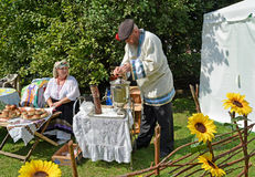 KALININGRAD, RUSSIA - AUGUST 15, 2014: The elderly man kindles a samovar at fair of national creativity Stock Photos