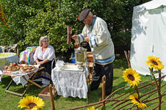 KALININGRAD, RUSSIA - AUGUST 15, 2014: The elderly man kindles a samovar at fair of national creativity Royalty Free Stock Photo