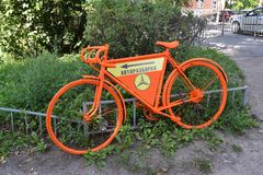 KALININGRAD, RUSSIA. The old bicycle of orange color with the index of Autodismantling costs on the street Stock Image
