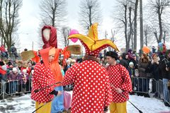 KALININGRAD, RUSSIA. Buffoons stand against the background of an effigy. The celebration of Maslenitsa in the park. KALININGRAD, RUSSIA - FEBRUARY 18, 2018 stock photography