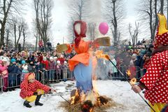 KALININGRAD, RUSSIA. Buffoons with torches burn down an effigy. The celebration of Maslenitsa in the park. KALININGRAD, RUSSIA - FEBRUARY 18, 2018: Buffoons with stock photos