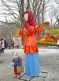 KALININGRAD, RUSSIA. The little girl looks at Maslenitsa effigy in the city park. KALININGRAD, RUSSIA - FEBRUARY 18, 2018: The little girl looks at Maslenitsa stock images