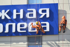 KALININGRAD, RUSSIA. Industrial climbers wash a  sign on the building by means of a sink of a high pressure Royalty Free Stock Photos