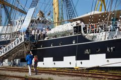 KALININGRAD, RUSSIA - JUNE 19, 2016: Tourists near the famous barque Kruzenshtern in the pier of Kaliningrad Sea Port. Launched in 1926, she was surrendered to Stock Photos