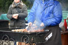 Kaliningrad, Russia La donna frigge un kebab su un addetto alla brasatura della via da vendere Fotografie Stock Libere da Diritti