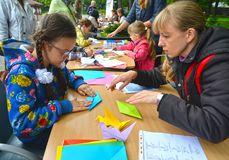 KALININGRAD, RUSSIA. The girl puts origami. Children`s master class in the open air. KALININGRAD, RUSSIA - SEPTEMBER 17, 2017: The girl puts origami. Children`s royalty free stock photography