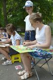 KALININGRAD, RUSSIA. The teacher teaches the girl to drawing of a landscape. A children`s open-air in the park. KALININGRAD, RUSSIA, JUNE 13, 2019: The teacher royalty free stock photography