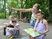 KALININGRAD, RUSSIA. The teacher teaches the girl to drawing of a landscape. A children`s open-air in the park. KALININGRAD, RUSSIA, JUNE 13, 2019: The teacher royalty free stock photos