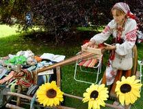 KALININGRAD, RUSSLAND - 15. AUGUST 2014: Der Weber in einer nationalen Klage arbeitet mit dem Hilfsschilf (Fokus auf Händen) Lizenzfreie Stockfotos