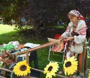 KALININGRAD, RUSSLAND - 15. AUGUST 2014: Der Weber in einer nationalen Klage spinnt mit dem Hilfsschilf Lizenzfreie Stockbilder