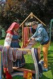 KALININGRAD, RUSSLAND - 15. AUGUST 2014: Der Weber unterrichtet den jungen Mann, mit dem Hilfsschilf zu spinnen Lizenzfreie Stockbilder