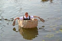 Kaliningrad, Russland Der Mann schwimmt in das alte englische Boot - der Coracle Das Feiertag ` Wasser-Versammlung ` im Museum de Stockbild