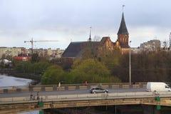 KALININGRAD RYSSLAND - APRIL 25, 2016: Sikt av den gotiska Konigsberg domkyrkan och planskild korsningbron över den Pregolya flod Royaltyfri Bild