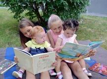 Kaliningrad Ryssland Barn av den olika åldern med intresse betraktar böcker som sitter på ett gräs i en trädgård arkivfoton