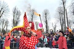 Kaliningrad Ryssland Clownen med en fackla i en hand förklarar bränning av en avbildning Berömmen av Maslenitsa i parkera fotografering för bildbyråer