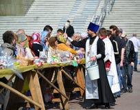 Kaliningrad Ryssland Den ortodoxa prästen inviger troenden, och påsken bakar ihop för påsk Royaltyfria Foton