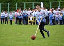 Kaliningrad Ryssland Den unga mannen rullar för honom en boll med hjälp av en pinne på de gladlynta starterna för konkurrenser Arkivfoton