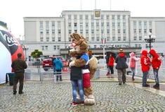 Kaliningrad Ryssland En maskot av den FIFA världscupen av den FIFA Zabivaka vargen 2018 omfamnar flickan Fotografering för Bildbyråer