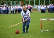Kaliningrad Ryssland Kvinnan av genomsnittliga år rullar för henne en boll med hjälp av en pinne på de gladlynta konkurrenserna Fotografering för Bildbyråer