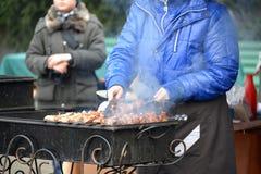 Kaliningrad Ryssland Kvinnan steker en kebab på en till salu gatafyrpanna Royaltyfria Foton