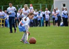 Kaliningrad Ryssland Lilla flickan rullar för henne en boll med hjälp av en pinne på de gladlynta starterna för konkurrenser Arkivbild