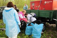 Kaliningrad Ryssland - Maj 18, 2019: Ekologisk h?ndelse p? kusten f?r baltiskt hav, reng?rande shoreline f?r folk fr?n avskr?de royaltyfri fotografi