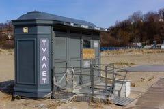 Kaliningrad Ryssland - mars 31, 2019: Stängd toalett på stranden för baltiskt hav på solig vårdag fotografering för bildbyråer