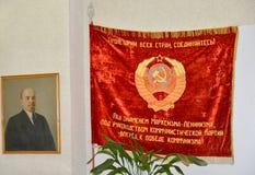 KALININGRADO, RUSIA - 10 DE NOVIEMBRE DE 2013: Símbolos de la era soviética - V I El retrato y una bandera roja de Lenin Imagen de archivo libre de regalías