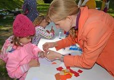Kaliningrado, Rusia El profesor ayuda al niño a hacer applique Clase del amo del ` s de los niños en el aire abierto foto de archivo