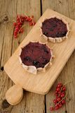 Kalitki, Russian rye cakes with berry filling on a wooden board and red currants. On wood board and wooden background Royalty Free Stock Photos