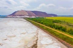 Kalium zoute die kuil dichtbij landbouwgrond en afvalreservoir wordt gesitueerd Industrieel landschap stock fotografie