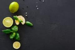 Kalk en citroen met munt op zwarte achtergrond stock afbeelding