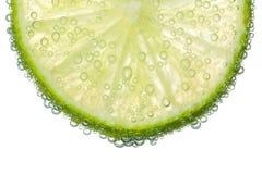 Kalk-Scheibe im klaren sprudelnden Wasser-Blasen-Hintergrund Stockfotografie